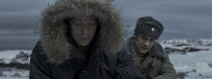 Two men sit in the foreground in an arctic or subarctic environment.