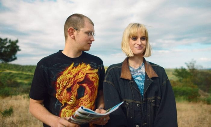 A man and a woman stand in a meadow. The man holds a magazine and looks at the woman, who looks ahead and smiles knowingly.
