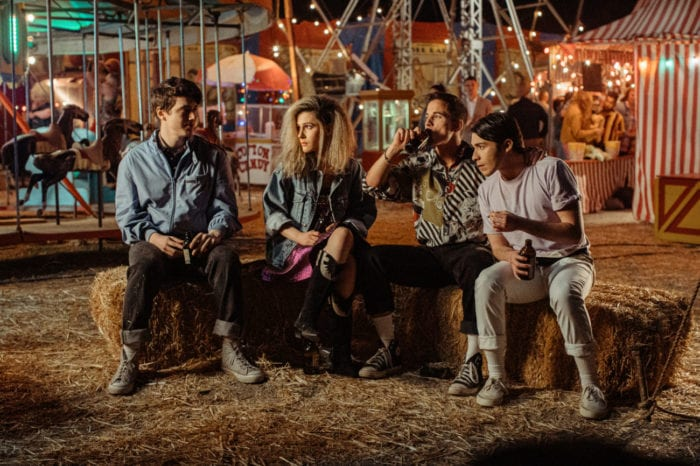 A group of young people sit on hay bales at an amusement park.