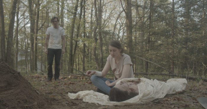 A young man and woman stand around a shrouded woman's corpse in a forest.