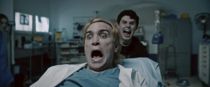 Two young men in a lab look into the camera and scream.