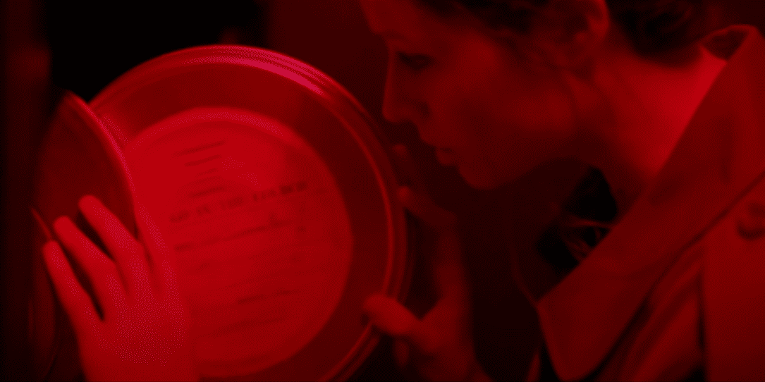 A woman examines a film reel in a red lit room