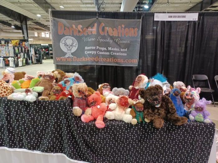 A table housing many stuffed animals modified with blood, sharp teeth, and other such gore.