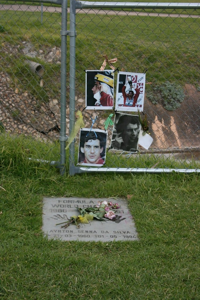 A memorial at the site of Ayrton Senna's grave displays flowers and photographs of the campion racer