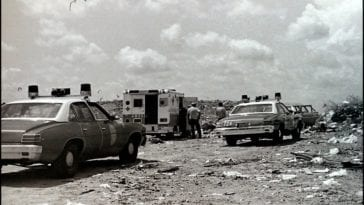 Two police cars and an ambulance search a landfill for a corpse