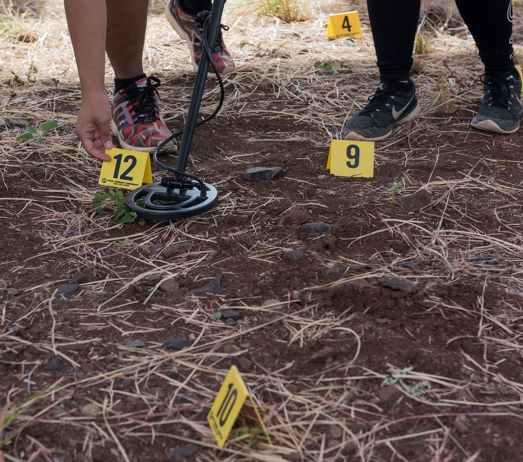 A shot of a grassy area marked off like a crime scene with yellow cards marking off where evidence has been found. Two people stand in the background. Only their feet are visible.