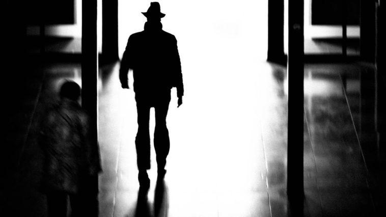 A shadow figure of a man walks down a dark hallway.