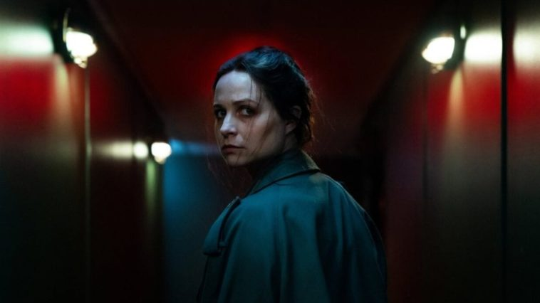 Enid looks back over her left shoulder walking down a theater corridor