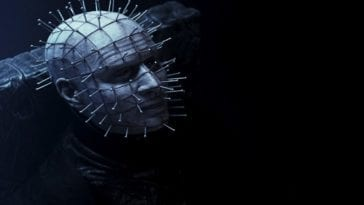 Pinhead (Paul T. Taylor), a pale man with nails sticking out of every angle of his face, sitting in a dark room. His face is somewhat illuminated by a ghostly blue light.