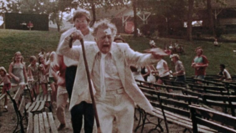 Lincoln runs with a cane up in the air from a crowd in The Amusement Park