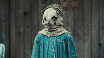A little boy wearing a sack mask with a face drawn on it and brown fabric hair and a blue uniform looks off-camera in front of a dilapidated barn.