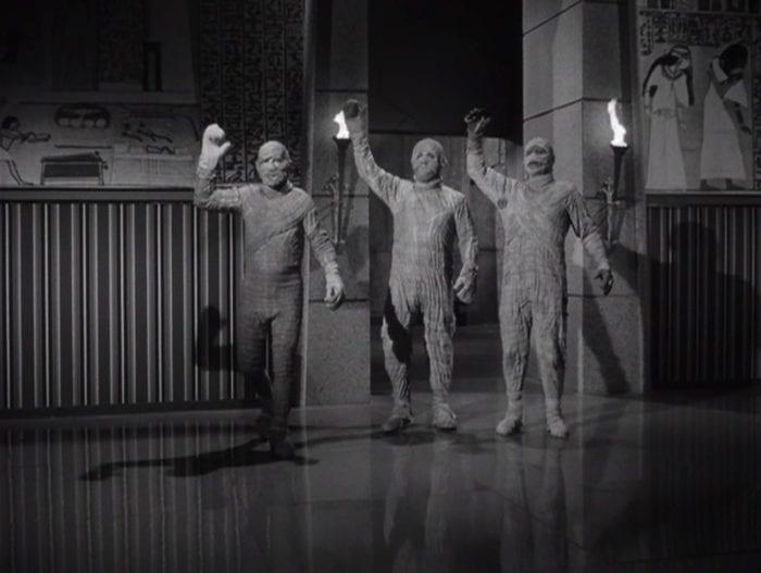 Three mummies with their hands raised