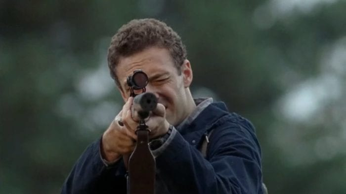 Aaron (Ross Marquand), a pale man with fluffy light brown hair, aiming a rifle towards the camera. His left eye is squeezed shut, and his right is obscured by the rifle. Behind him is what looks like a very blurred out forest.
