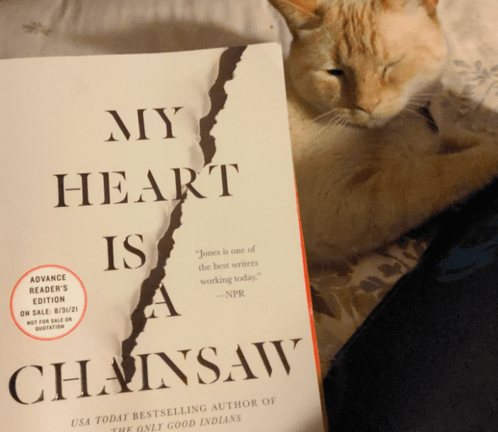 an early reader's copy of My Heart Is A Chainsaw by Stephen Graham Jones next to a small cream coloured cat