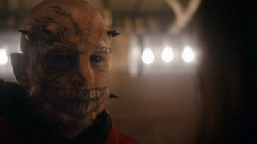 The Devil (Damian Maffei), a pale man with pitch black eyes in a room lit by a few exposed lightbulbs. He has tattoos on his face, most notably a large, sharp-toothed smile across his mouth. He has three black spike implants on either side of his jawline, and two on each of his temples.
