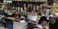"""A booth at decorated with many creepy masks, trinkets, figures, and a smaller display of colored contacts. There is a QR code to the right that says """"scan me""""."""