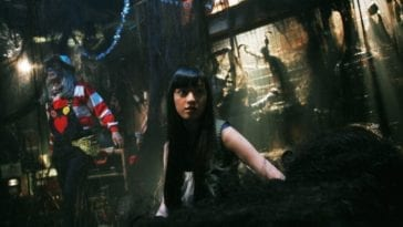 A young Japanese woman with long black hair, in a room filled with hair extensions. A man poses behind her.
