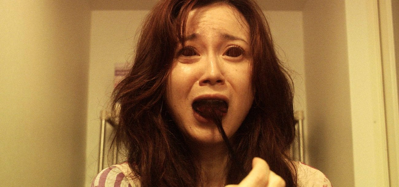 A young woman with a scared expression as she pulls a clump of hair away from her mouth.