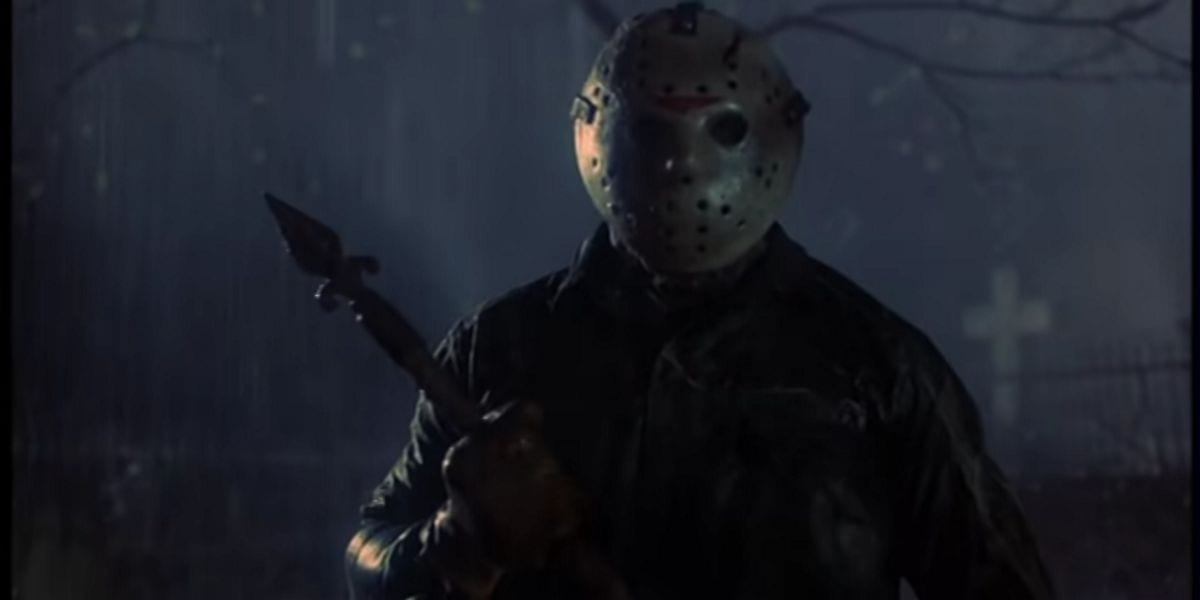Jason Voorhees (C.J. Graham) standing in a cemetery at night in the rain. He is holding some sort of spear-type metal object.