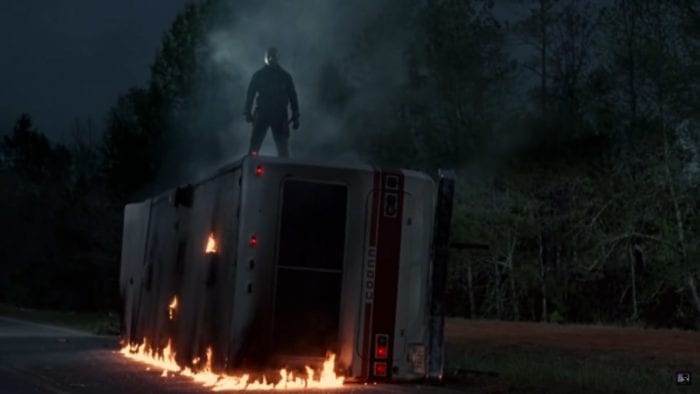 Jason Voorhees (C.J. Graham) standing on top of a toppled, flaming RV. He is slightly obscured by the smoke and his mask is illuminated by moonlight.