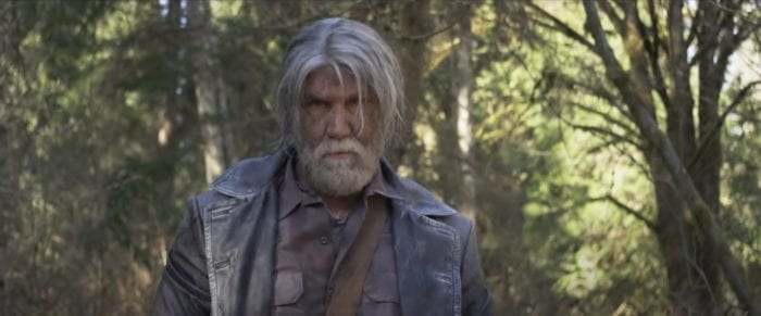 Elias Voorhees (C.J. Graham), an old white man with unkempt gray and white hair and a white beard, standing in a forest. His face is dirty and his expression is serious.