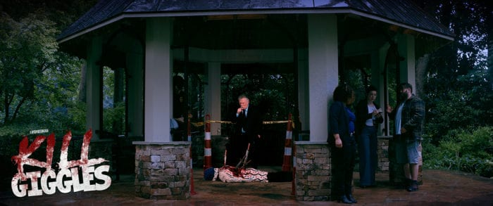 A gazebo in a forest on an overcast day. In its center lays a clown with blue hair, face down with several knives sticking out of their back. An older white man in a suit stands over them, in front of some caution tape and cones. There are several onlookers off to the right of the image.