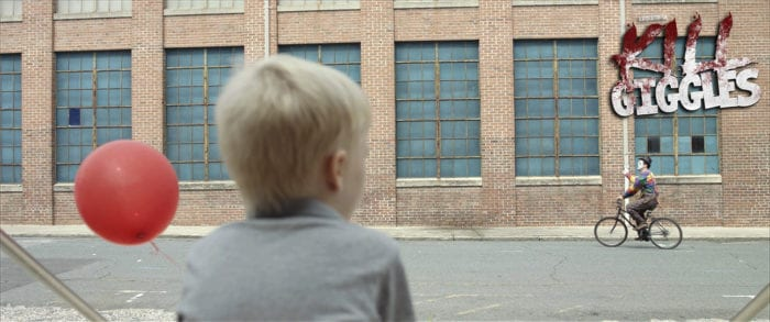 Young Tommy (Aiden Mowrer), a pale, blonde boy wearing a gray shirt and holding a red balloon. The camera is to his back as he watched a clown riding a bicycle past his school.