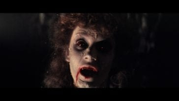 A pale feminine face with long curly dark hair peers out of the darkness with large dark eyes and blood dripping from her mouth.