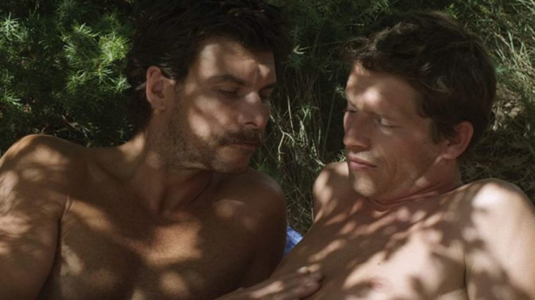 Two shirtless men on a beach in the shade of a tree, with one caressing the other's chest.