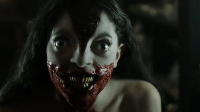 Hannah Fierman as Lily in Siren. There is a split in her face beginning at the bridge of her nose. Her eyes are wide and dark, her straight black hair framing her pale face. Her teeth are sharp and her large mouth is covered in blood.