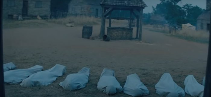 A bunch of bodies in bags in front of a well