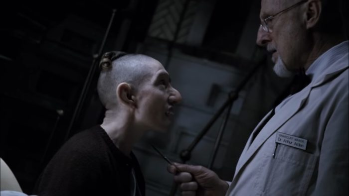 Naomi Grossman in American Horror Story: Asylum as Pepper, a short, mostly-bald pale girl with a deformed face and large nose, glaring up at Dr. Arthur Arden (played by James Cromwell) in a dark room. Dr. Arden, an old white man with white facial hair wearing a white lab coat, is holding a sharp object to Pepper's throat.