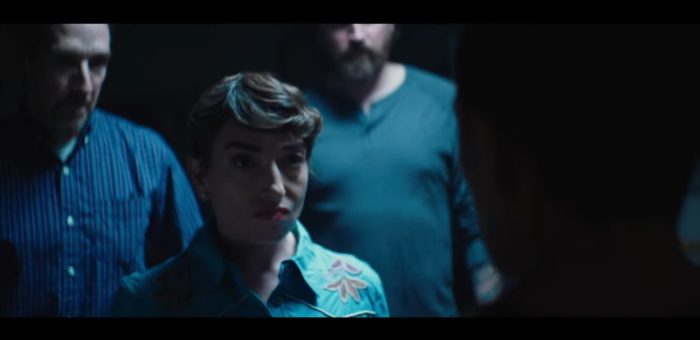 Naomi Grossman in 1BR as Janice, a short, pale woman with short dark brown hair wearing a blue button-up shirt with floral designs etched into the shoulders. Two men in similar shades of blue shirts are standing behind her. She is glaring at someone whose head is in front of the camera.