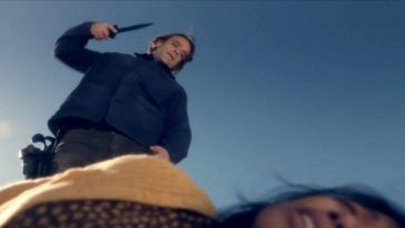 Nick Stahl in Fear The Walking Dead as Riley, a white man with long-ish brown hair wearing a dark blue coat and jeans. The camera is pointed upwards at him, a woman on the ground blurred at the base of the shot, as Riley stands over her, backdropped by the blue sky. He is wielding a knife in his right hand, poised to attack.