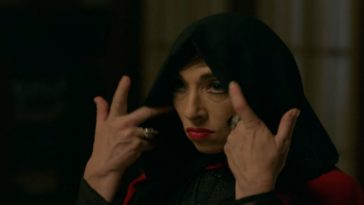 Naomi Grossman in American Horror Story: Apocalypse as Samantha Crowe, a white woman with red lips and dark eye makeup wearing a black hoot over her head. Her hands are raised to pull the hood back.