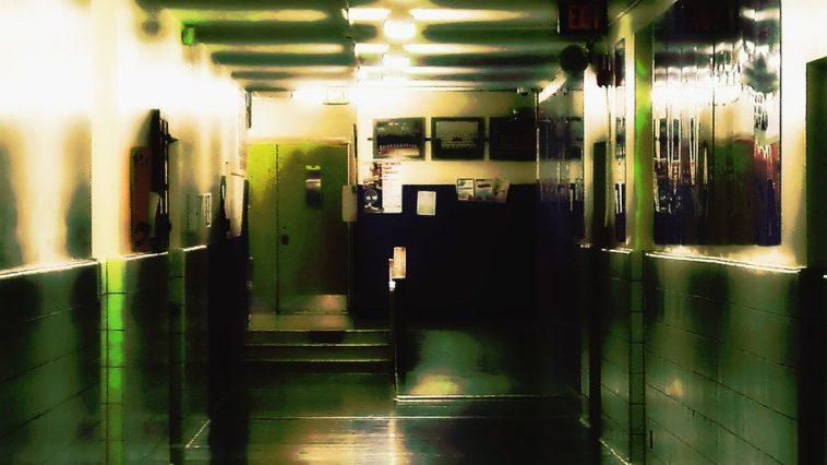 A badly lit, decrepit school hallway is barren of life