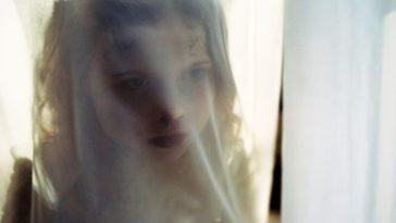 A ghostly girl seen through a thin curtain