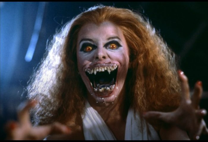 Amy From Fright Night transformed to half vampire. Her mouth is wide open and she has a big wide mouth filled with sharp fangs.
