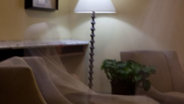 A translucent hooded figure dressed in white sits in a chair in a living room.