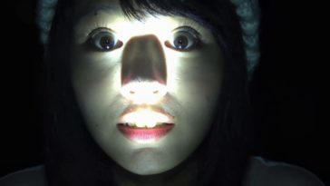 A woman's face lit from the bottom