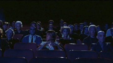 A theatre full of blank faced men and women stare at a movie screen