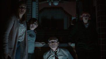 A family of four in a dark bathroom stare at the camera in terror.
