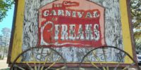 """Weathered sign reminiscent of a carnival billboard announces """"Carnival Freaks"""""""