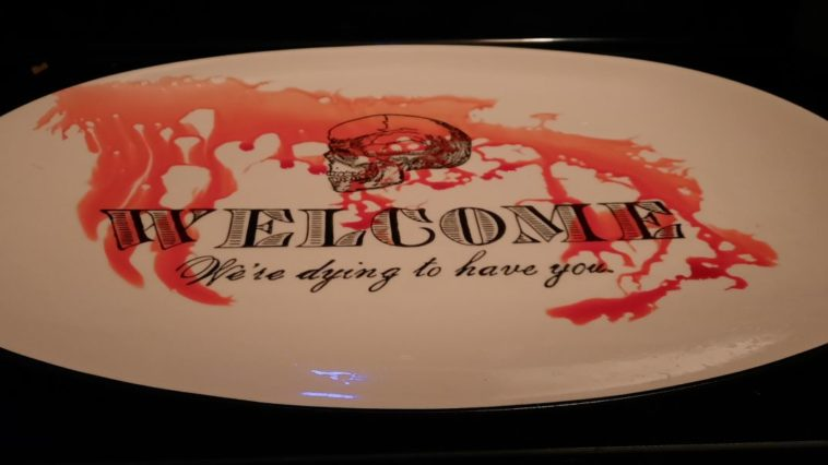 """A serving tray reads """"WELCOME, We're dying to have you"""" Blood runs down the surface of the tray."""
