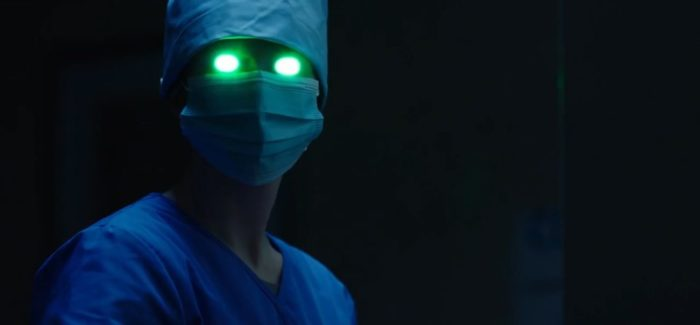 In Queen Bee, a doctor in scrubs looks toward the camera with glowing green eyes