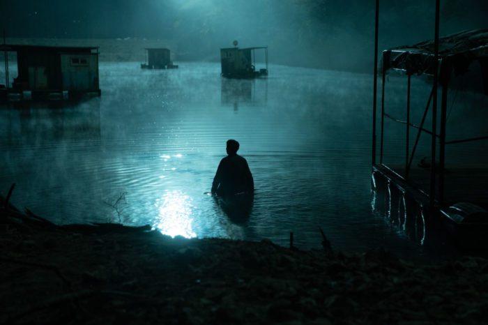 a man enters a moonlit misty lake