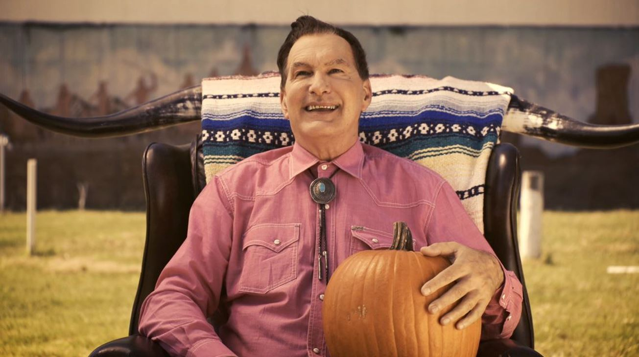 Joe Bob sitting in a chair at a drive-in, a pumpkin on his lap