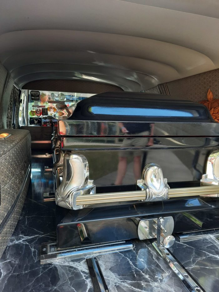 inside the back of a hearse. A casket is loaded into the back and a view of the interior is seen.