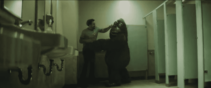 The Janitor punches an animatronic gorilla in a men's restroom