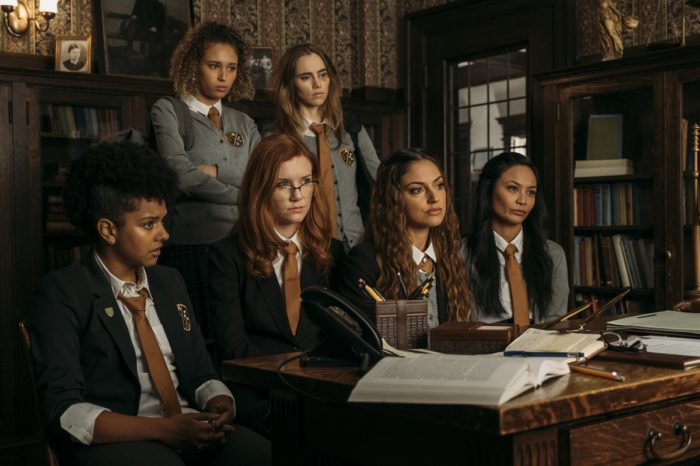 The girls gather around the deans desk after Camille and Alice fight to hear what their punishment is.